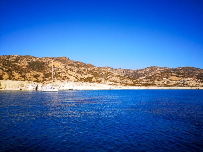 Wyspa Poliagos - wybrzeże i cumujący w zatoce jacht